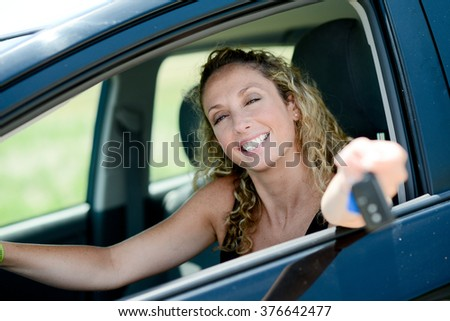 cheerful happy young woman driving her new car - stock photo