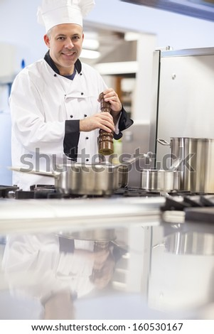 Cheerful head chef flavoring food with pepper in professional kitchen - stock photo