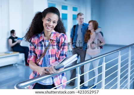 Cheerful high school student in school hallway before lecture - stock photo
