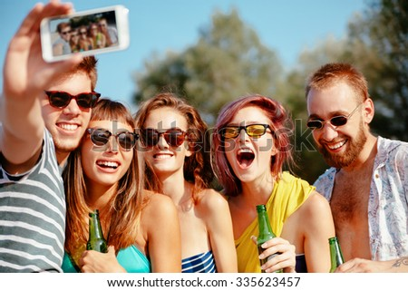 Cheerful Hipster Friends At The Beach Taking Selfie Using Smart Phone - stock photo
