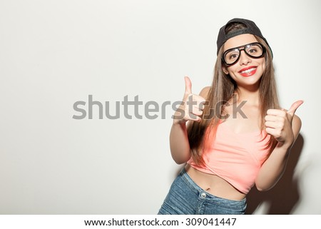 Cheerful hipster girl is standing and giving thumbs up. She is wearing eyeglasses and black cap. The girl is smiling and looking at the camera happily. Isolated and copy space in left side - stock photo