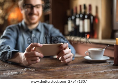 Cheerful hipster guy at the restaurant using a mobile phone, hands close up - stock photo