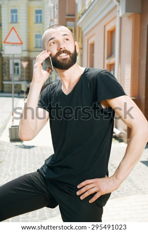 Cheerful hipster guy is raising mobile phone to his ear and talking with someone. He is puzzled and looking towards in the street - stock photo