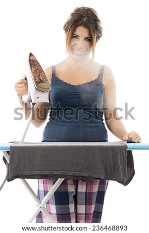 Cheerful housewife with a beautiful smile standing at the ironing board ironing clothes  - stock photo