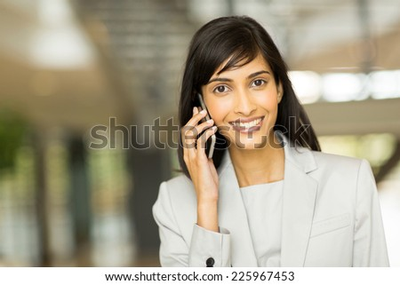 cheerful indian business executive talking on cell phone - stock photo