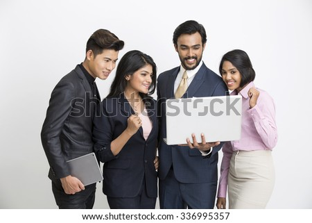 Cheerful Indian business people team happily looking at the laptop on white background. - stock photo