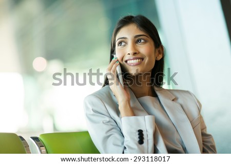 cheerful indian business woman talking on mobile phone at airport - stock photo