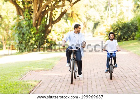 cheerful indian father and daughter riding bikes in the park - stock photo