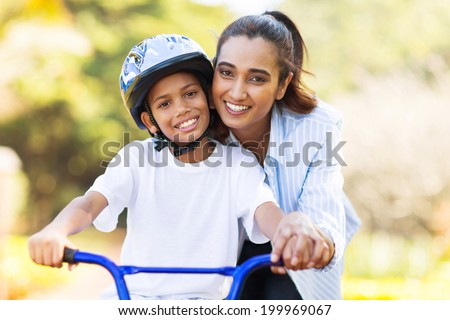 cheerful indian mother teaching her son to ride a bike - stock photo
