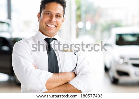 cheerful indian vehicle salesman with arms crossed - stock photo