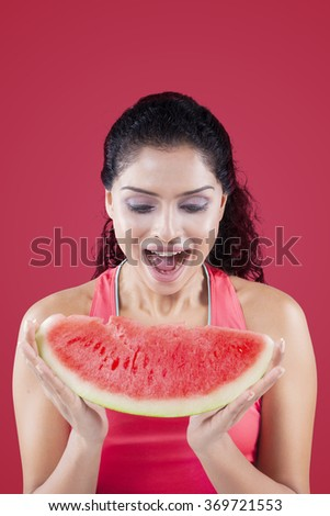 Cheerful indian woman eating watermelon with red background. Concept of healthy food, superfood - stock photo