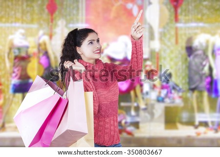 Cheerful indian woman holding shopping bags in the mall while wearing winter clothes and pointing at copy space - stock photo