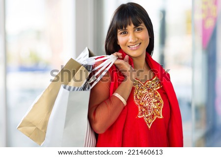cheerful indian woman shopping in mall - stock photo