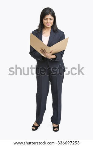 Cheerful Indian young business woman standing with document, isolated on white background - stock photo