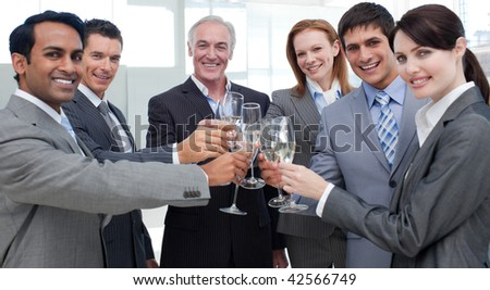 Cheerful international business people celebrating a sucess with Champagne - stock photo