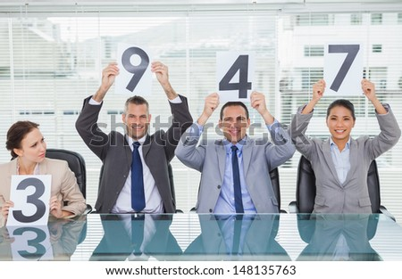 Cheerful interview panel holding signs giving marks in bright office - stock photo