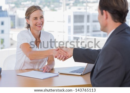 Cheerful interviewer shaking hand of an interviewee during a job interview - stock photo