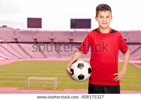 Cheerful junior football player in a red jersey posing in a football stadium and holding a ball - stock photo