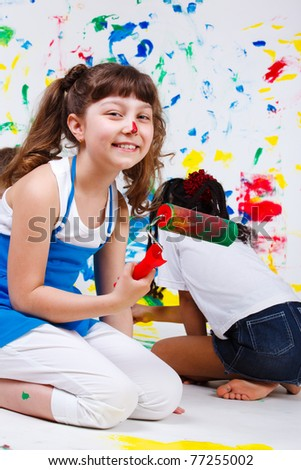 Cheerful junior student holding paint roller in hand - stock photo