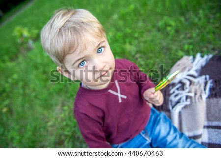 Cheerful kid eating candy in the park in the summer. Little boy in the summer park licking a lollipop. - stock photo