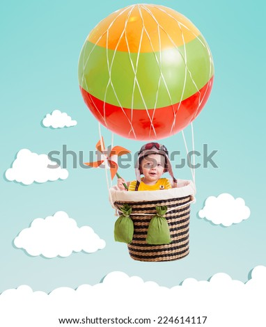 cheerful kid on hot air balloon in the sky - stock photo