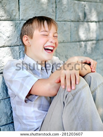 Cheerful Kid sit by the Wall of the House - stock photo