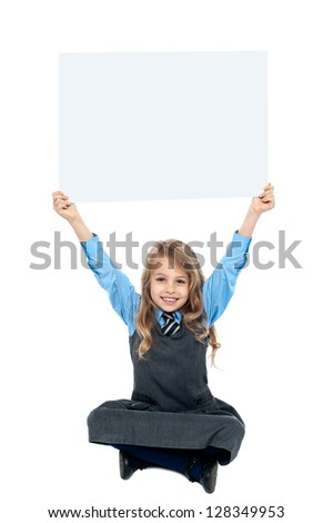 Cheerful kid sitting on floor and holding ad board above her head. - stock photo