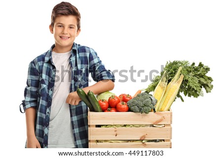Cheerful kid standing next to a crate full of vegetables isolated on white background - stock photo