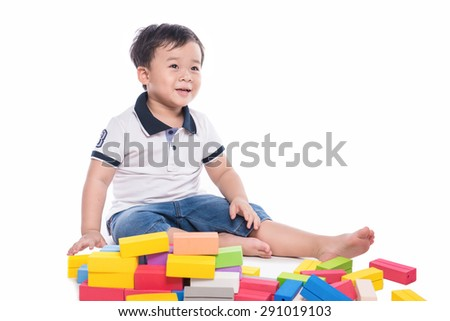 cheerful kid with construction set. Adorable laughing toddler boy playing with colorful blocks sitting on white background - stock photo