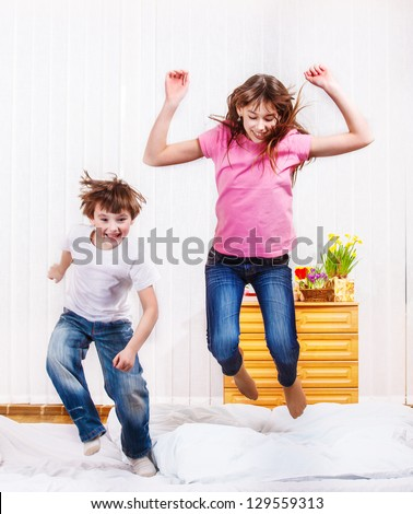 Cheerful kids jumping on the bed - stock photo