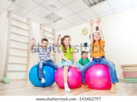 Cheerful kids on large gym balls with their hands up - stock photo
