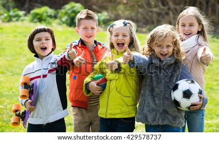 Cheerful kids with ball having fun outdoors in sunny day - stock photo