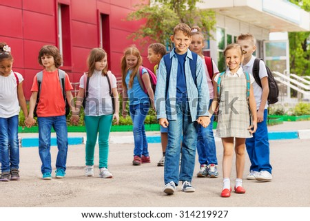 Cheerful kids with rucksacks near school building - stock photo
