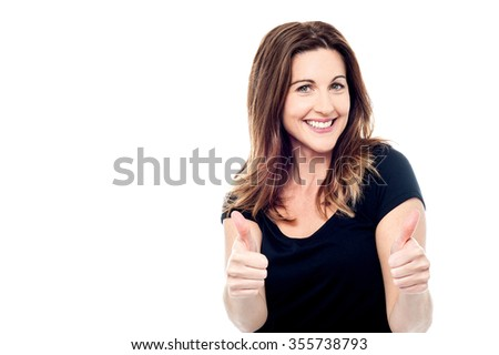 Cheerful lady showing thumbs up sign towards camera - stock photo
