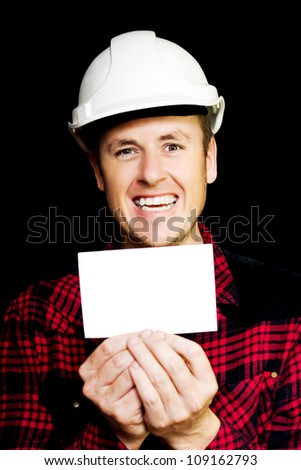 Cheerful laughing builder with a beaming smile holding up a blank business card with both hands for you to input your contact details, qualification or identification on a black studio background - stock photo