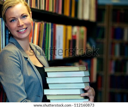Cheerful librarian or student standing inside a library carrying a stack of large books either for education and research or inventory that has to be replaced on the shelves - stock photo