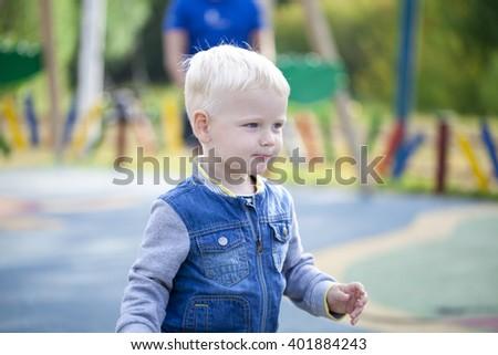 Cheerful little blonde boy running around on the playground, summer outdoors - stock photo