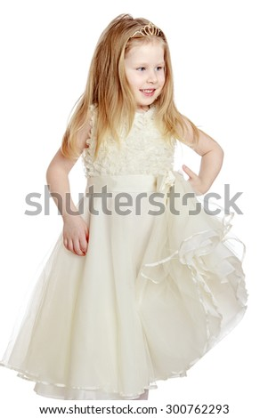 Cheerful little blonde girl with flowing long hair in white ball long dress and white stockings . Girl hand holds the edge of her dress , and today she goes to a children's party with their parents - stock photo