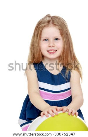 Cheerful little blonde girl with her long hair in a striped blue dress. The girl is going through the hands of the ball, close-up-Isolated on white background - stock photo