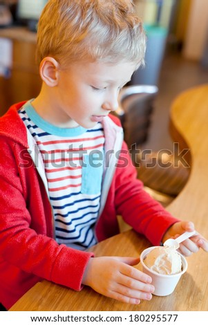 cheerful little boy eating ice-cream in cafe - stock photo
