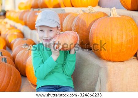 cheerful little boy holding pumpkin enjoying halloween time at pumpkin patch - stock photo