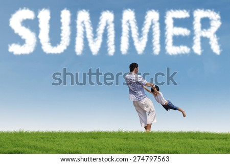 Cheerful little boy playing on the field and rotated by his father under a summer's cloud - stock photo