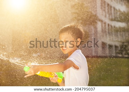 Cheerful little boy playing water guns in the park - stock photo