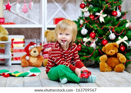 Cheerful little boy playing with his red toy car by the Christmas tree - stock photo