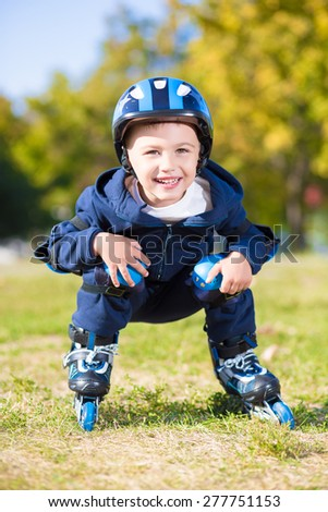 Cheerful little boy riding on roller skates squatting - stock photo