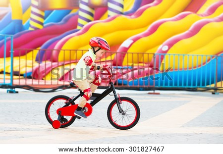 Cheerful little boy riding on the bicycle in amusement park, happy carefree childhood, having fun outdoors in summer camp  - stock photo