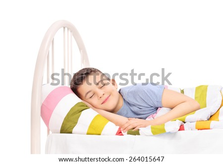 Cheerful little boy sleeping in a comfortable bed and dreaming sweet dreams covered with a blanket isolated on white background - stock photo