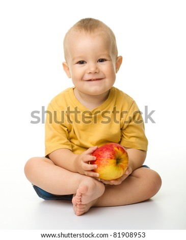 Cheerful little boy with red apple is smiling while sitting on a floor, isolated over white - stock photo