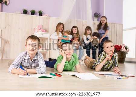 Cheerful little boys are lying on the floor and drawing on paper - stock photo