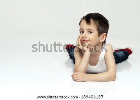 Cheerful little boys are lying on the floor and looking at camera  - stock photo